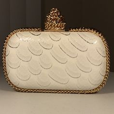 Glamorous clutch with a glamorous touch White clutch with metallic detailing, trimmed in gold chains, and comes with a gold chain to double as a shoulder bag. Bags Clutches & Wristlets