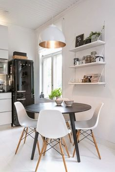 Beautiful white dining room with a round black table and white Eames Chairs. What great white and golden pendant light!