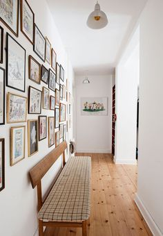 Retro-inspired entryway and hall with a vintage wooden bench and numerous frames with comics.
