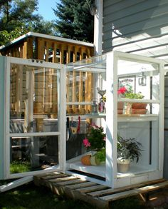 Small outdoor greenhouse out of reclaimed storm windows.