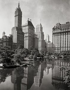 New York City art. Night view of plaza buildings, over park lake, year 1933.Vintage New York City photography.
