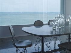 Enjoy a panoramic view of the Dutch seaside from this dining room, complete with Eames wire chairs. Photo: Hotze Eisma, Elle Decor