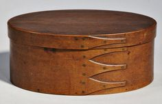 Skinner's - The Shaker Collection of Erhart Muller, Auction 2898M. June 4, 2016. Lot: 94.  Estimate: $800-1,200.  Realized: $984.  Description:  Shaker Brown-stained Pine and Maple Covered Oval Box, Mount Lebanon, New York, three fingers on the box, copper points and tacks, ht. 3 5/8, lg. 8 5/8, dp. 5 7/8 in.