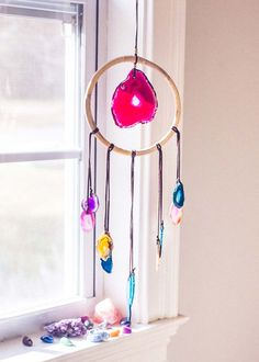 Brighten up! This stunning wall hanging is made with a rattan hoop, featuring a large agate at the center and lots of little vibrant agates dripping down, strung on soft leather lace. This statement p