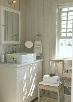 source: Heiberg Cummings Design  Cottage bathroom features wood paneled walls framing ivory medicine cabinet over ivory vanity accented with carrera marble top and white vessel sink paired with antique style bridge faucet. Chic bathroom with ivory chair used to hold towels next to ivory tray table with bath accessories.