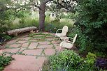 Sheltered garden room, flagstone patio, stone bench, and chairs under Ponderosa pine tree next to meadow in drought tolerant Colorado garden with Viburnum plicatum and Prunus americana.
