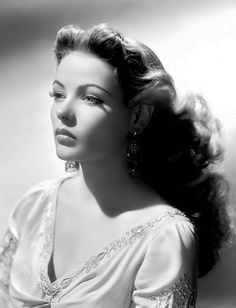Gene Tierney. this is b 's hairdo you have hot rollers. You could roll your hair in some big rollers..you wouldn't need many or you could do a couple big curls and then take those front pieces and roll them around your finger an bony pin them!