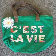 """C'est La Vie tote bag Adorable flowered tote bag! Never used, a pure kelly green color, with a floral """"C'est La Vie"""" across it! Great for a picnic or heading to the beach! The flower is attached to the bag. Claire's Bags Totes"""
