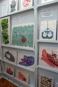 beautiful display at a craft show booth of woodcut prints by Tugboat Print Shop - great craft show display idea