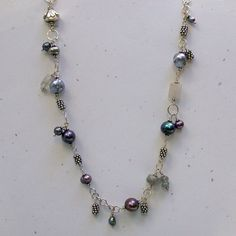 Freshwater pearl and gemstone necklace. Silvery gray freshwater pearls in all shades and sizes are linked together with sterling silver rings and chain. Rutilated quartz, India silver beads, labradori