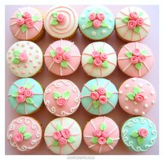 Pastel fondant covered cupcakes decorated with piped icing and sugar flowers