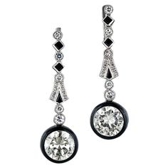 These dramatic and dazzling 1 5/8 inch long Deco drops feature a matched pair of transitional-cut diamonds weighing 6.10 carats total. Their faint yellow hue is effectively contrasted with sleek black enamel borders suspended from streamline diamond and black onyx tops. Distinguished and artsy jewels. 6.70 carats total diamond weight, circa 1925, platinum.