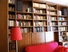 Una libreria in noce su misura realizzata in un appartamento a Roma. La boiserie dietro al divano sostiene anche il peso degli elementi appesi della libreria.