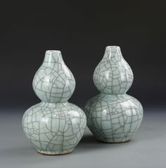 China, 19th C., pair of Ge Yao gourd vases, in double gourd form, in a grey celadon glaze with a wide network of black and gold crackle lines.