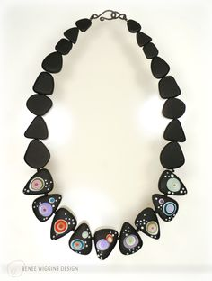 "Renee Wiggins Design. ""Midnight Carnival"" necklace with handmade lampworked glass beads adorned with pools of luscious color and raised dots, and etched matte. Accompanied with black cultured sea glass beads and handmade hammered and oxidized sterling silver clasp. 6-2016"