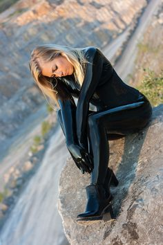 Blonde in black latex catsuit and ankle boots outdoors.