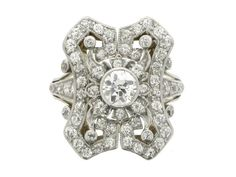 Antique diamond cluster ring, circa 1910. A yellow gold and platinum ring set with one central round old cut diamond in a platinum rubover collet setting with an approximate weight of 0.45 carats, surrounded by an ornate symmetrical openwork bezel composed of a vertical octagonal frame with concave edges, above a scalloped gallery, flanked by raised split shoulders, all set with sixty four round old cut diamonds in platinum topped gold millegrain bead and collet settings with an approximate…