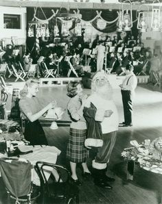 While Betty Grable Get Ready To Hang Christmas Decorations, Bette Davis Helps Dress Eddie Cantor In A Santa Claus Costume For The Hollywood Canteen's First Christmas