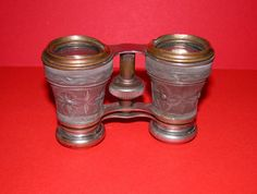 Authentic antique opera glasses. They are brass, chrome and the lense case is matt grey decorated metal case. These glasses are in good working order. A few minor dints but these are to be expected considering their age and usage. The lenses are good. Easily cleanable. All lenses can be removed and screwed back in place. The magnification is clear and clean. Size Width 3.5 inches Length 2.5 in. Extended 3.0 in. Lense to Lense 4.0 in.  Packed with care Wrapped in tissue and tied with ribbon