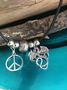 16 - 18 adjustable black leather cord necklace with 4 rounds beads, one large decorative Bead, Peace Sign & 1 1/4 Dragon Charm.  Got the inspiration