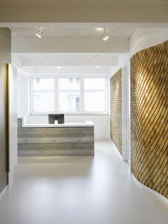 Concrete reception desk. Diamond shaped shingles as wall covering