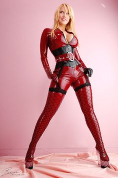 Bianca Beauchamp | latex fetish model | red catsuit | black corset | big belt | blond hair | sexy | busty | perfect body