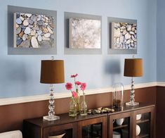 a chair rail separates rich chocolate brown and light blue. Silvery rectangles painted on the wall frame the 3-D art.
