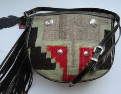 Beautiful Saddlebag with vintage Navajo textile fragment, leather feathers, decorative conchos and leather fringe. See similar bags at www.pccohandbags.com