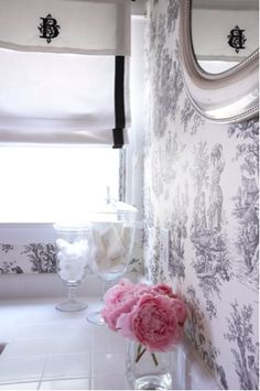 Love this space!     The white fabric roman shade with black ribbon border and black monogram is divine! Love toile like wallpaper in bathrooms! white & black chinoiserie elegant bathroom design with glass canisters and round silver chrome mirror are the perfect touch in this space. Gray white bathroom colors with pink accents!