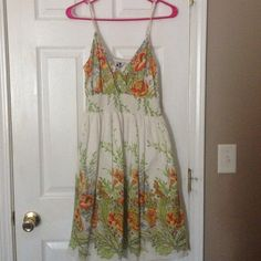 Floral Sundress Orange, yellow, and lime green on an off white background. Elasticized band at waist, adjustable spaghetti style straps. Skirt portion is fully lined. Purchased at local boutique. Dresses