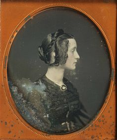 Daguerrotype which shows how the hair was done for the 1850 style. A braid and hair pinned up in back; sides were puffed out and come forward. Style which fit well in the bonnets of the time.