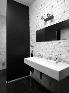 Kontrastowe zestawienia. Chodzi zarówno o dobór kolorów (czerń i biel), jak i faktur (nierówna cegła i gładkie powierzchnie - podłoga wyłożona płytkami i ścianka zasłaniająca sedes).