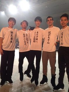 """From left to right the T-shirts read: """"猫足着氷"""" (wearing cat feet on ice (rough translation as it's just a bunch of kanji)) // """"まずい餃子も美味しいんです"""" (bad dumplings (gyouza) are delicious too) // """"負けず嫌い、または頑固"""" (I hate to lose, and I'm stubborn (it really says """"i hate to lose, or stubborn"""" word to word, but given from Yuzu's personality, I think that's what it means)) // """"はびちゃん"""" (Javi-chan) // """"なむくん"""" (Nam-kun)"""