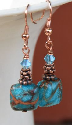These earrings consist of 12mm flat square blue imperial Jasper gemstones, antique copper Tibetan spacer beads and daisy spacer beads, 4mm blue faceted crystal beads, and copper headpins and earwires. The earrings are 2 inches long.  Some people react to copper negatively, such as finding the copper turns their skin green. Others do not react or find copper medicinal.  The colors of the earrings can look different on different Monitors and Mobile Devices.  All jewelry ships in an organza…