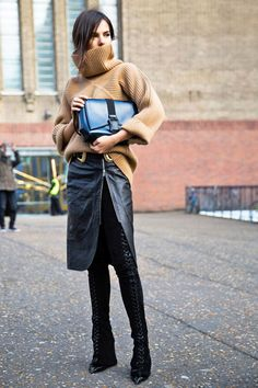 An oversized turtleneck sweater is worn with a side zip leather midi skirt and over-the-knee boots