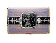 AN ART DECO ROCK CRYSTAL, ENAMEL AND DIAMOND CIGARETTE CASE, BY MAPPIN & WEBB The rectangular lavender guilloché enamel case, centering upon a carved rock crystal square plaque, etched with an Oriental floral scene, within a rose-cut diamond surround, flanked on either side by a rose-cut diamond and black enamel band, with sugarloaf cabochon moonstone accents and a rose-cut diamond pushpiece, mounted in 18k gold, circa 1915