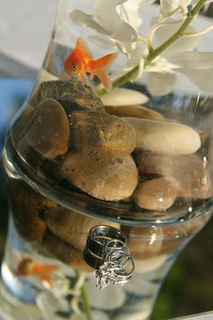 Having a water themed wedding? Create unique water centerpieces by using fish bowls with pebbles in the bottom and goldfish swimming in it.