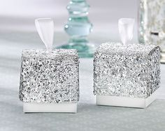 Get your shine on! These elegant favor boxes add a touch of brilliance to your table and are perfect for packaging a take-home treat. Shimmery silver metallic sparkles can go vintage or modern to blend with your days details. These are great for weddings, bridal showers, baby showers or any party favor. Features and facts: Cardstock favor box with silver glitter top and white satin ribbon pull Sold in sets of 48 Measures 2.15 h x 2w Boxes ship flat - some easy assembly required  Also comes…