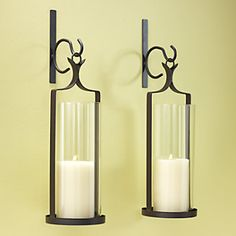 "Set of 2 Wall Sconces | Fill the room with rustic style. Glass candle shade; metal frame with a brown painted finish. Assembly required. Holds up to 4"" ball or pillar candle."