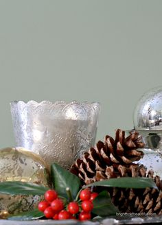 Create beautiful and festive holiday vignettes with  mercury glass ornaments, pinecones and holly leaves with red berries