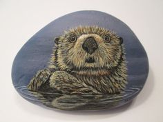 Otter hand painted on a rock by Ann Kelly.