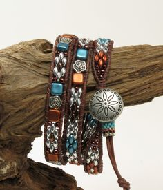 This stylish, rustic bracelet has been beaded using a mixture of glass and metal beads that have been woven onto dark brown 1.5mm leather. The bracelet features 3 different designs that incorporate superduos, Czech two hole tiles and antique silver flower beads. The clasp is a conch style silver plated button. The button slides into a loop on the end that has a peyote tube slider to adjust the size. The total length of this bracelet is 23 1/4 from the button to the knot on the end and will…