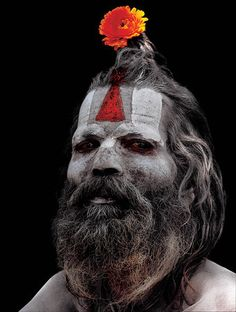 This sadhu's vertically oriented tilaka that converges on the bridge of his nose shows him to be a Vaishnava, or follower of Lord Vishnu, known as the Preserver in the Hindu Pantheon of Gods. The flower in his hair is completely of his own design. Although the forehead markings, or tilakas, are relatively uniform in relation to one's order, sect, and sub-sect, individual variations in both the tilaka and other body art are the norm, not an exception.Pashupatinath, Kathmandu, Nepal.