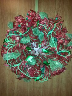 Red and green striped Christmas Wreath with polka dot red ribbon and green mesh rolled accents and green mesh tubing.