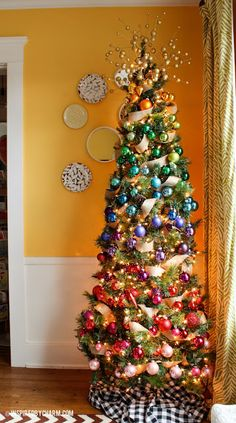 This rainbow decorated slim tree adds Christmas to a corner