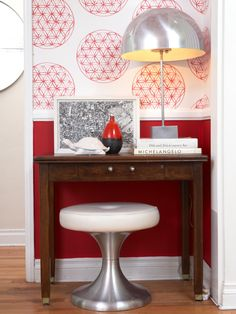 Designer Emily Henderson used solid classic red below this home's white wainscoting, then added a contemporary vibe atop the rail with red-and-white patterned wallpaper. (=)