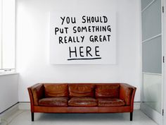 """[image]: Blank white canvas, except for the words """"You should put something really great HERE"""" in black. Hangs above a brown leather couch."""