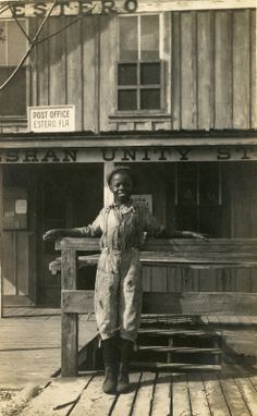 """Unidentified young man in front of the Koreshan Unity general store on the Estero River.   Date: Postmarked"" January 11, 1911. Credit: State Library and Archives of Florida"