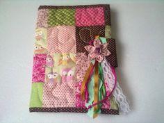 Linda capa de agenda/caderno em patchwork. <br>Confeccionada em tecido de algodão com aplique em fuxico e fitas. <br>Foto ilustrativa <br>Somente sob encomenda
