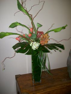 clear vase green goddess calla, fresh lotus pods. orchids,fun leaves and grass, tulips